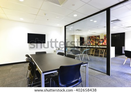 Modern meeting room with huge glass door opened and covered with glass walls, including tv and black tables