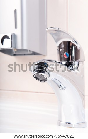 Modern metal faucet closeup. No water flowing.