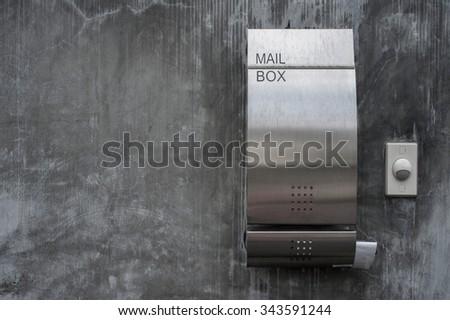 Modern metal mailbox on house concrete wall - stock photo