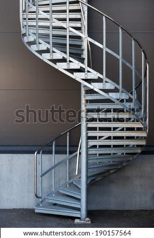 Modern metal spiral staircase above dark gray wall - stock photo