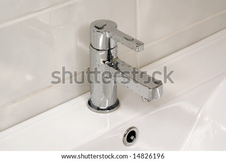 Modern metallic faucet with water drops
