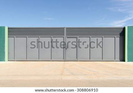Modern metallic gate painted in gray. Property access closed