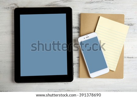 Modern mobile phone, tablet and notebook on white wooden background - stock photo