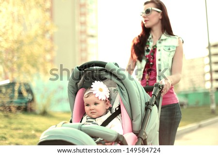 Modern mother with her baby walking down the street. Special warm color tuning.