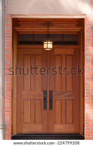 Modern Natural Wood Double Doors with Overhead Hanging Lamp in Brick Building - stock photo