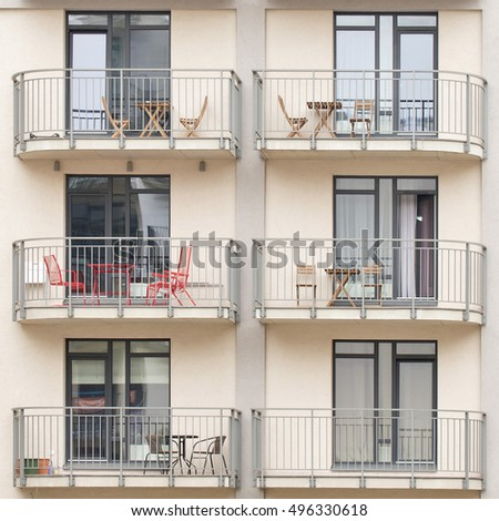 Modern new building with balconies full of tables, chairs