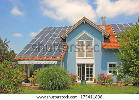 modern new built house and garden, rooftop with solar cells, blue front with lattice window. - stock photo