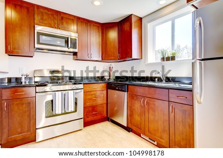 Modern new cherry kitchen with steal appliances. - stock photo