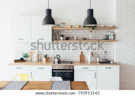 Modern new light interior of kitchen with white furniture and dining table.