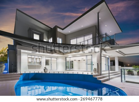 Modern new luxurious mansion exterior with swimming pool and reflections at dusk with pink and blue sky on the Gold Coast, Queensland, Australia - stock photo