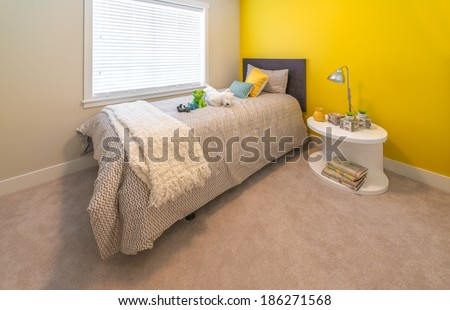 Modern nicely decorated bedroom for children painted in yellow. Interior design. - stock photo