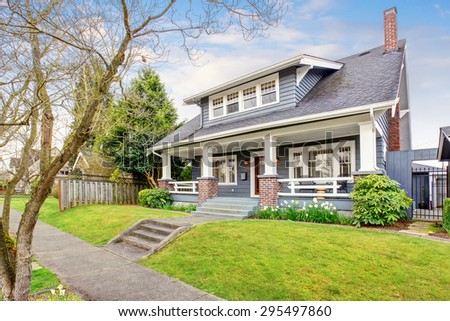 Modern northwest home with white trim, and grass filled front yard. - stock photo
