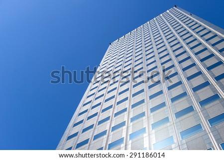 Modern office building against clear blue sky - stock photo