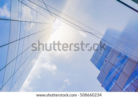 Modern Office building and blue sky background. The building reflects the blue sky in the windows. And sun shines bright behind the building.