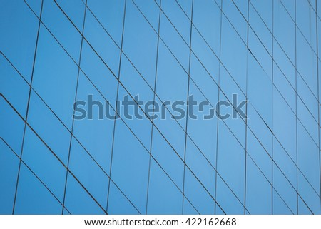 Modern office building with blue glass windows background