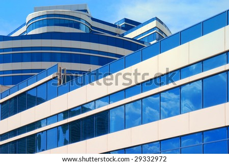 Modern office building with blue glass windows, reflecting clouds - stock photo