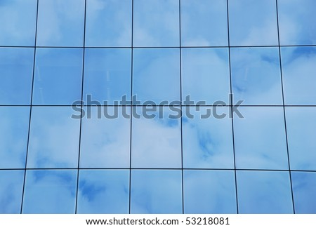 modern office building with glass pattern with clouds reflected - stock photo