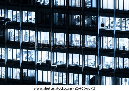 Modern office building with glowing windows at night, black and white toned in blue - stock photo
