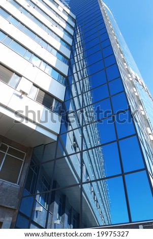 Modern office building with sky reflection in windows