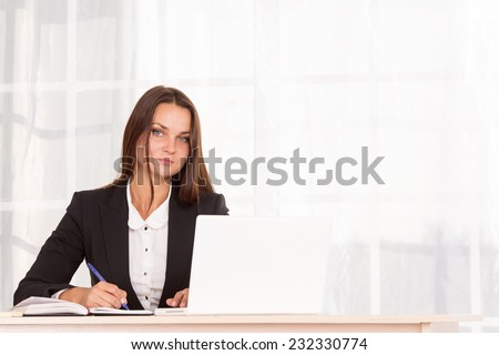 Modern office employee. Business woman working at office table on his laptop. Computer, internet, business, adverse communication - business concept and way of life of the office staff. She is student - stock photo