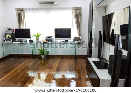 Modern office with computer and laptop with home theater - stock photo
