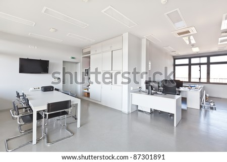Modern office with white furniture, cupboard, conference desk and walls and with plasma TV on the wall - stock photo