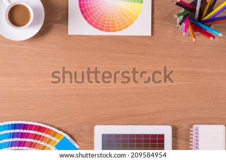 Modern office workplace with digital tablet, notepad, colorful pencils, cup of coffee, and color swatches on a desktop. View from the top  - stock photo