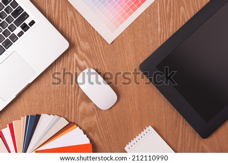 Modern office workplace with laptop, graphic tablet, notepad, color swatches and mouse on a desktop. View from the top. A concept of design workplace office - stock photo