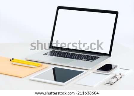 Modern office workplace with metallic laptop, digital tablet, mobile phone, papers, notepad and others business objects and items lying on a desk. Isolated on white background. - stock photo