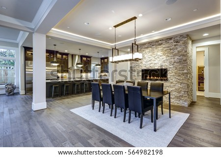 Modern Open Floor Plan Dining Room Design Accented With Stone Fireplace  Wall Facing Black Dining Table
