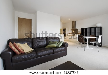 modern open plan living room with kitchen view in the background - stock photo