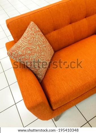 Modern orange sofa with decorative cushion. - stock photo