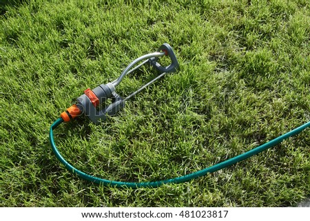 Modern oscillating sprinkler on the mown lawn in the garden