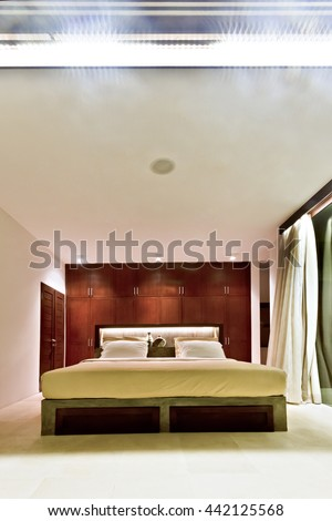 Modern outdoor bedroom decorated with wood in luxury house at night - stock photo