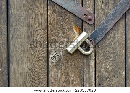 Modern padlock on textured black wooden door. Background and Texture for text or image - stock photo