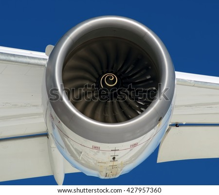 Modern passenger aircraft jet engine, wing, slats, flaps extended front in air close up