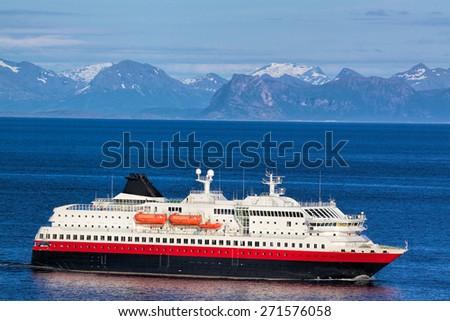 Modern passenger ship cruising along norwegian coast near Lofoten islands - stock photo