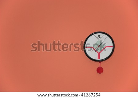 modern pendulum clock on red wall - stock photo