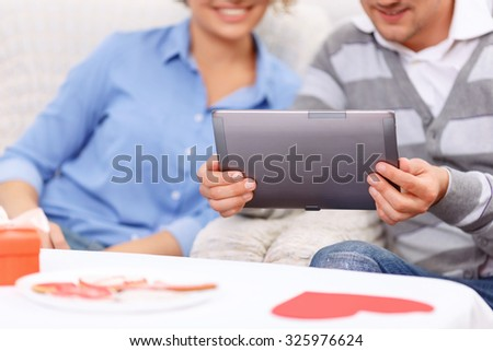 Modern people. Pleasant young positive nice couple holding laptop and sitting at the table while spending great  time together - stock photo