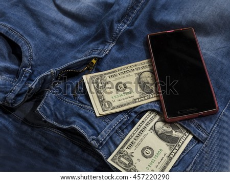 Modern phone with jeans pocket displaying screen. Cash dollars from pocket watch
