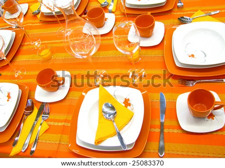 Modern plates, cups, glasses on orange table - stock photo