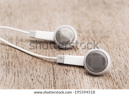 Modern portable audio earphones isolated on wood background  - stock photo
