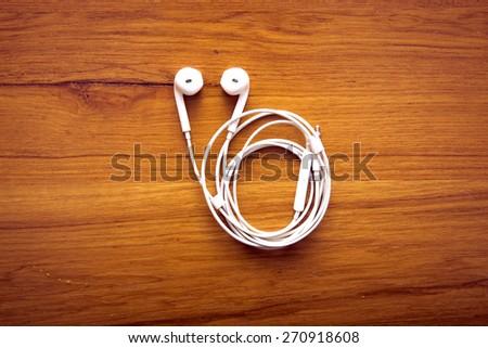 Modern portable audio earphones on wood board - stock photo