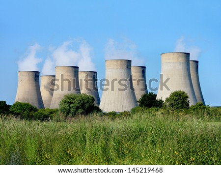 Modern power station cooling towers against a blue sky with copy space. - stock photo