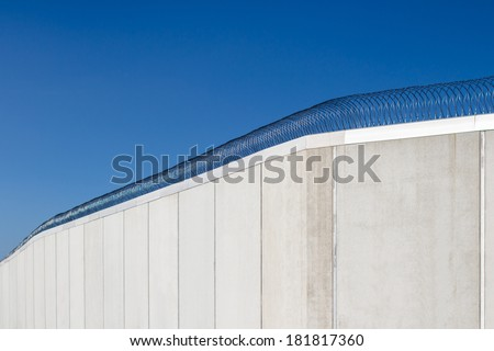 Modern prison wall against blue sky. - stock photo
