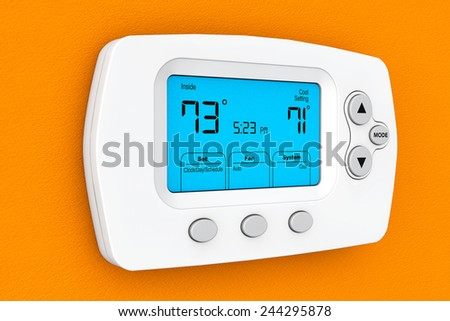Modern Programming Thermostat on a orange wall - stock photo