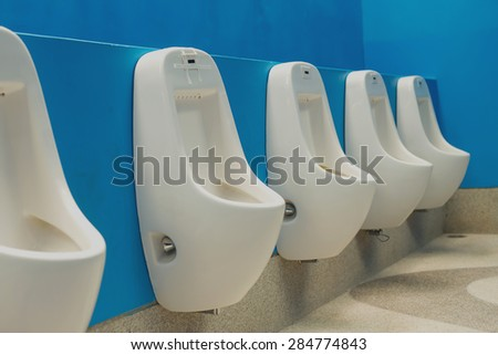 Modern public toilets Interiors A row of urinals urinating on a blue background