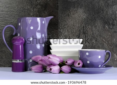 Modern Purple and White Polka Dot Kitchen with large platter plate, cutlery and kitchenware against black slate and white benchtop. - stock photo