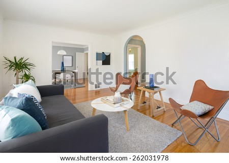 Modern quaint living room interior with designer chairs, white round table, rug and couch.  - stock photo