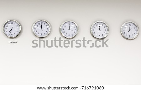 Modern quarz analog clocks on white wall in office. Horizontal orientation with text space below